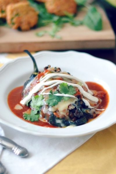 chorizo and black bean stuffed poblanos with enchilada sauce and spanish rice cakes