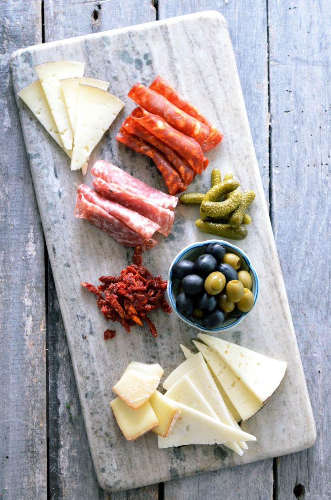 A selection of cheese, olives, pickles and charcuterie that one might use on a veggie and cheese board.