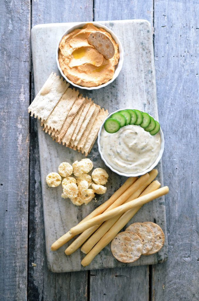 A selection of crackers and dips that one might use on a veggie and cheese board.