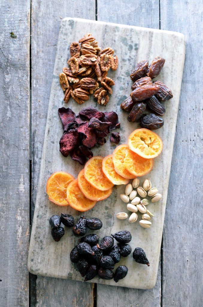 A selection of dried fruit and nuts that one might use on a vegetable and cheese board.